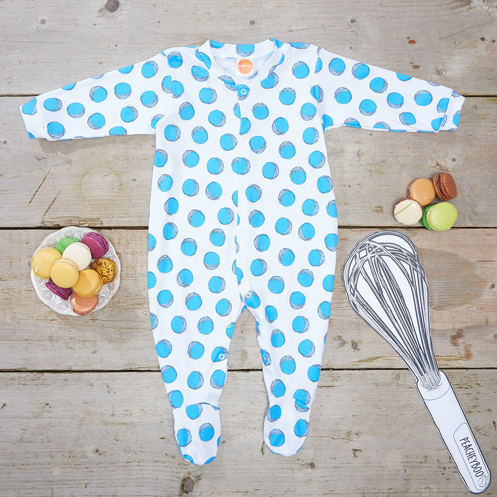 Children's & Baby Clothes Photography, flat lay of a blue macaron printed baby grow with props on a wooden board