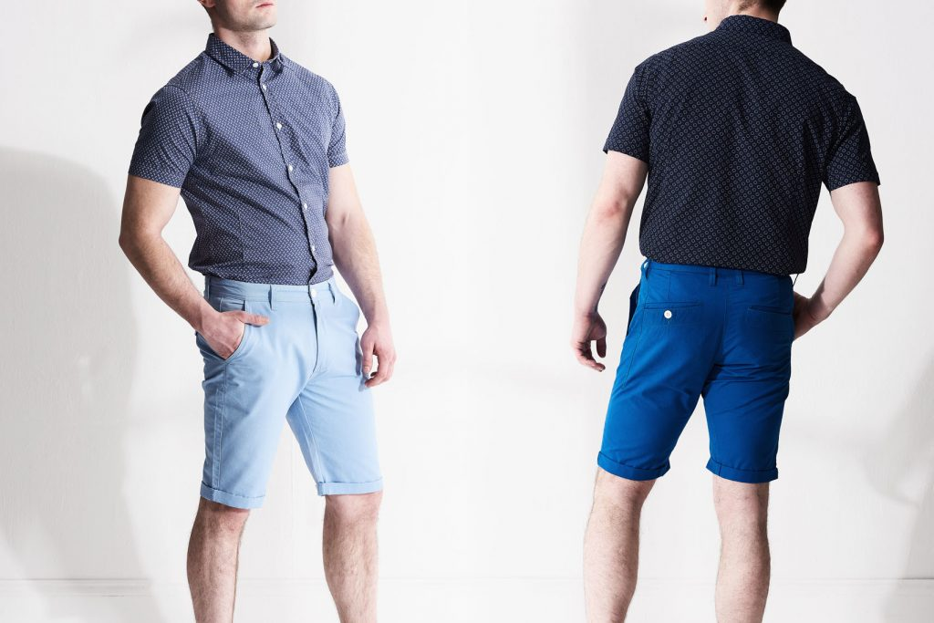 product photography of male model wearing blue shorts and printed short sleeve shirt