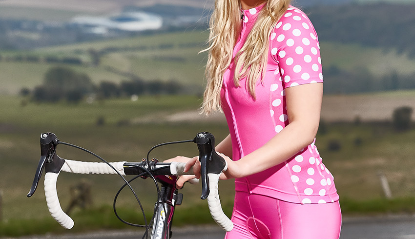 product photography of a model wearing pink polka dot lycra pushing a bike in the countryside