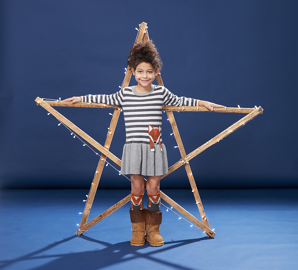 Children's & Baby Clothes Photography, girl smiling wearing a stripe fox t-shirt, socks and brown boots leaning a on a star light