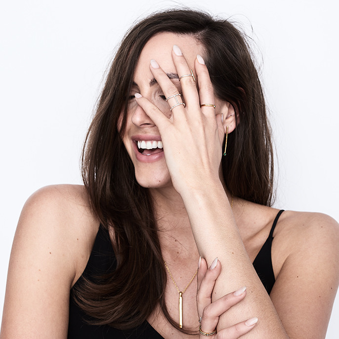 Jewellery photography, brunette female model laughing with her hand on her face wearing jewellery