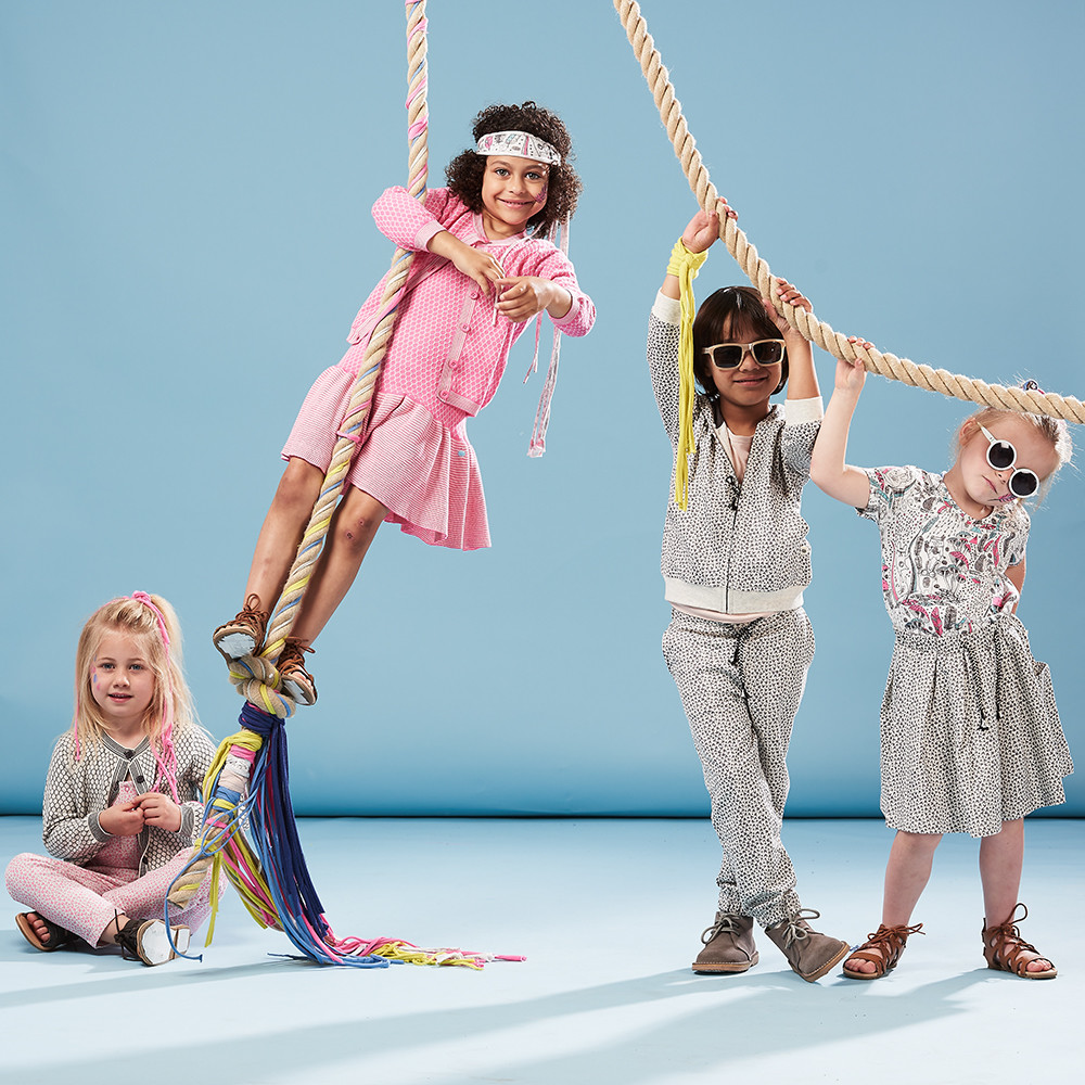 Children's & babywear photoshoot featuring four young models wearing pink and white patterned clothes in a studio set up with a blue background and a rope swing
