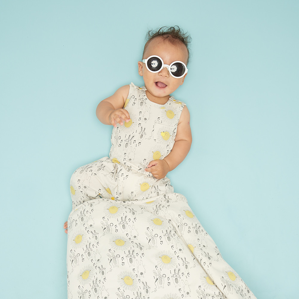 Children's & babywear photoshoot featuring a baby in a white patterned outfit laying on a blue background