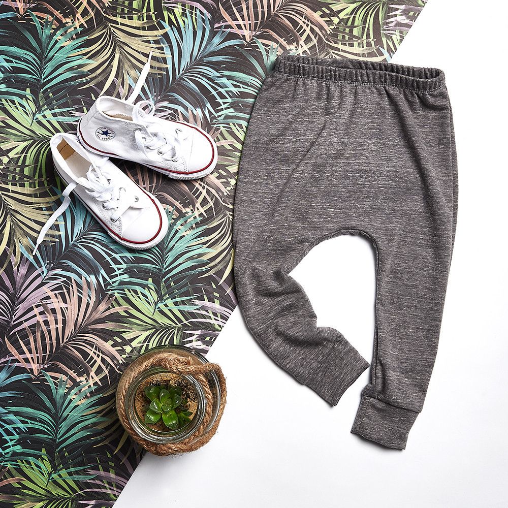 Baby clothes photoshoot at Capture Factory featuring grey leggings arranged in a flat lay with props including trainers, a plant and tropical fabric