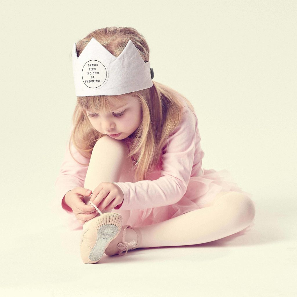children's accessories, girl sitting tying up ballet shoes wearing a crown