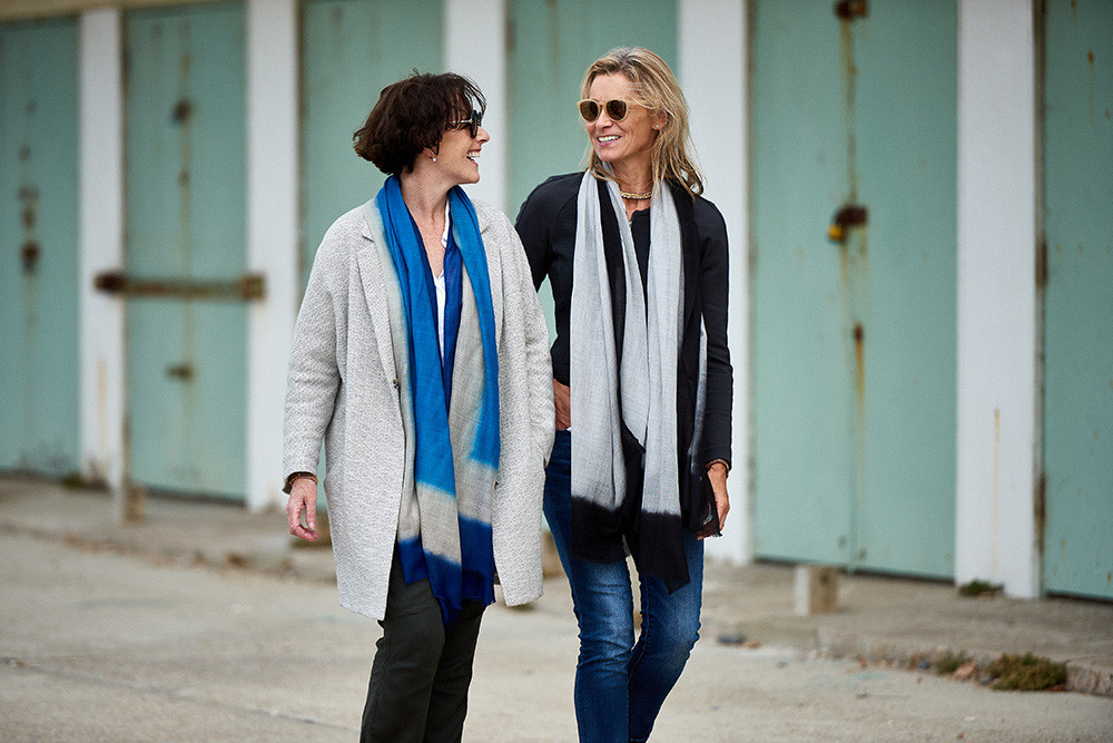 Brighton location photoshoot with two ladies modelling scarves outside green beach huts