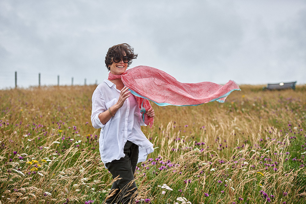 Sussex video production, Location photoshoot with model wearing pink scarf walking in the grass