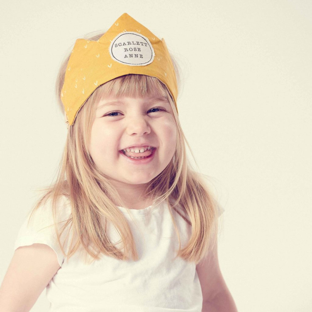 children's accessories, smiling girl wearing a yellow crown