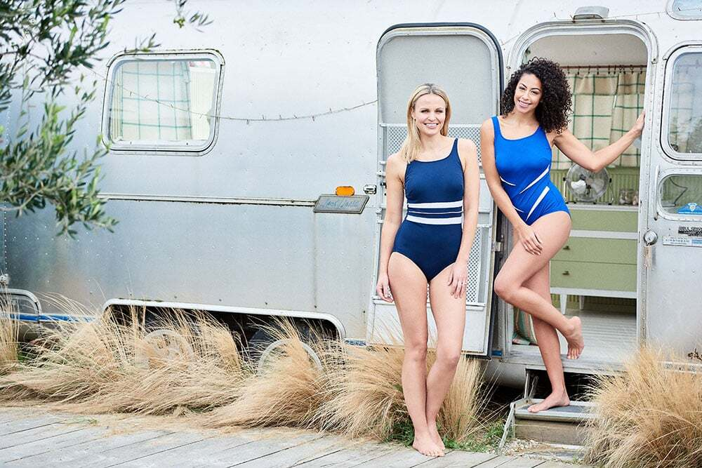 Location beach photoshoot, models wearing swimsuits in front of a caravan