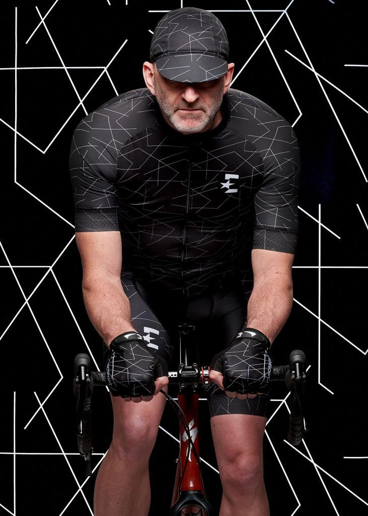 Cyclewear photography, male cyclist wearing black lycra top, hat and gloves