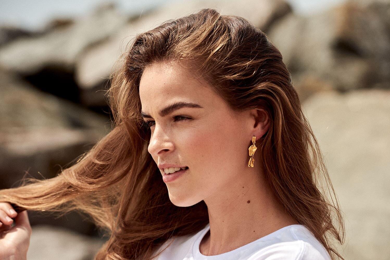 on location jewellery photo shoot, brunette model wears earrings
