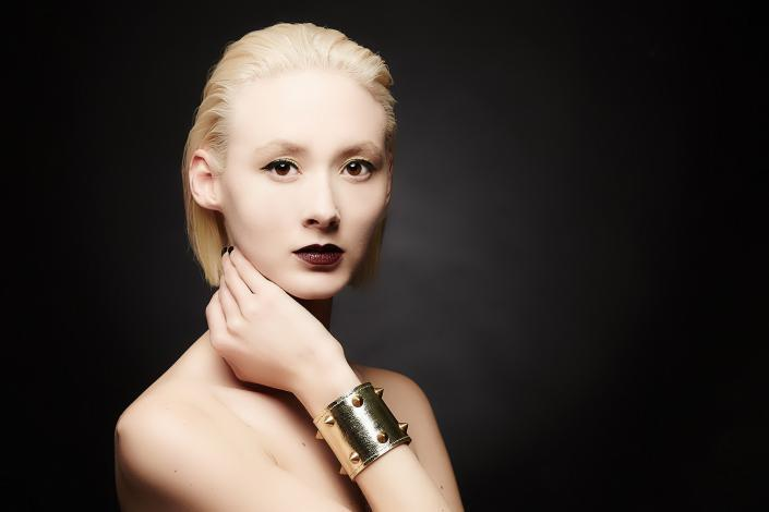 Blonde jewellery model shot black background gold bracelet