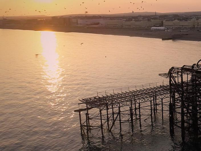 Brighton West Pier at sunset with views of the coastline taken on drone