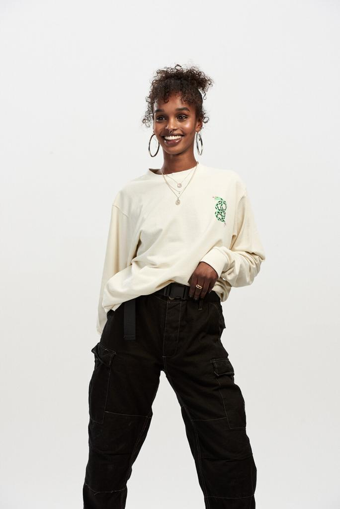 90s on-trend photoshoot, female model wearing cream jumper and black combat trousers