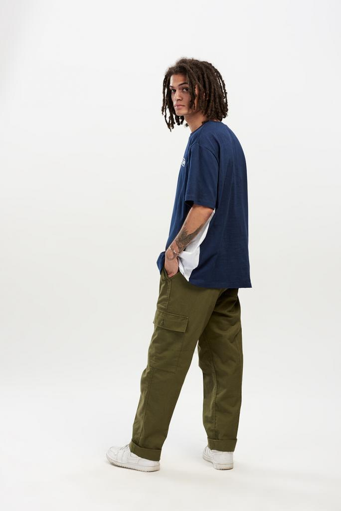 90s on-trend fashion photoshoot, casual fashion worn by a male model wearing an oversized navy short sleeved t-shirt and khaki trousers with pockets.