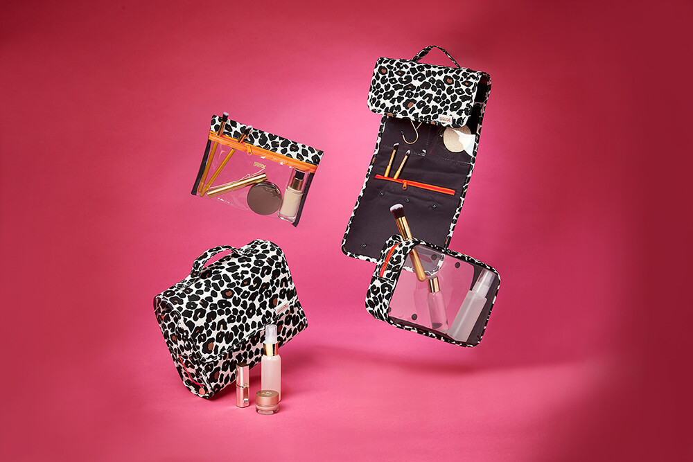 product photography studio, leopard print washbags & makeup floating against a pink background